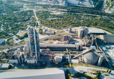 Aerial view of cement manufacturing plant. Concept of buildings at the factory, steel pipes, giants